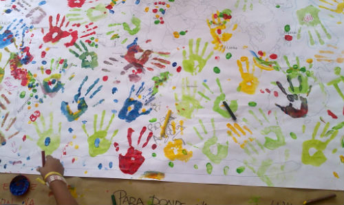 Colourful paint hand prints on a simple map