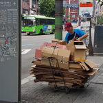 Photograph of a man clearing away cardboard in South Korea.