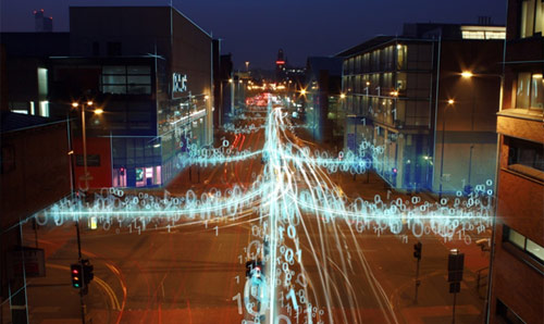 A busy street overlaid with strings of binary code to represent cities learning