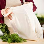 Woman unpacking green vegetables from a reusable fabric shopping bag.